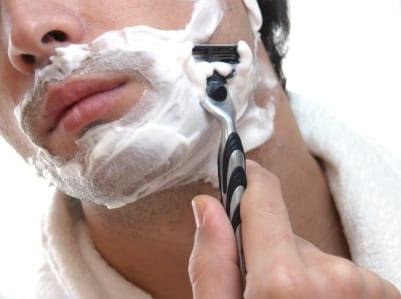 man shaving his face
